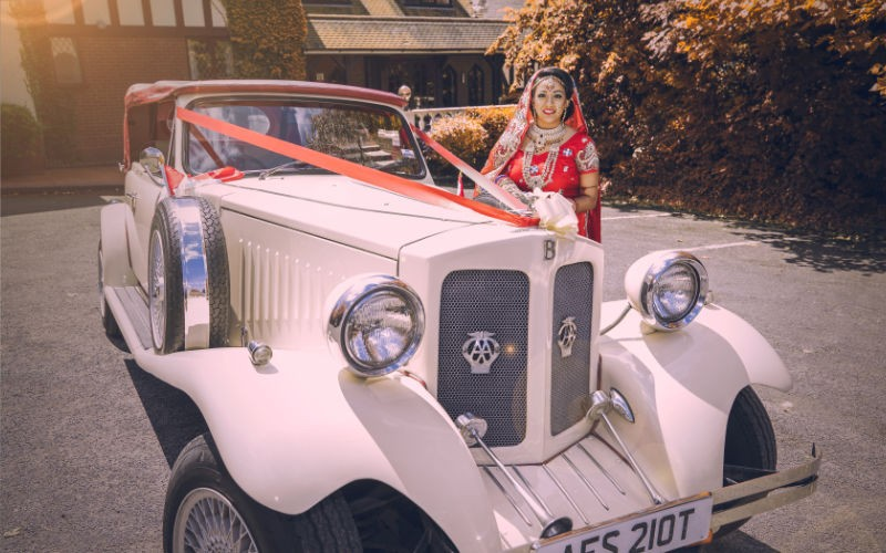 bride and groom in a classic car at their wedding in leicester
