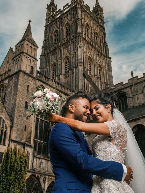 couple embracing in front of church at their wolverhampton wedding taken by videography experts at Harvest Creative Media