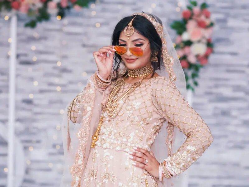 bride wearing sunglasses in her wedding dress at wedding in wolverhampton. Taken by Harvest creative media wedding videography